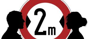"""Na ilustracji widać rysunek profilu twarzy kobiety i mężczyzny. Między nimi jest koło z czerwoną ramką. W środku koła jest napis """"2m"""". Napis przedstawia odległość między ludźmi, która powinna wynosić 2 metry."""