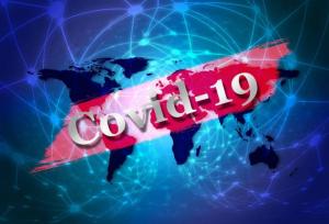 Zdjęcie przedstawiające schemat kontynentów. Na środku zdjęcia na czerwonym tle widać napis Covid-19. Napis ten przysłania kontynenty.