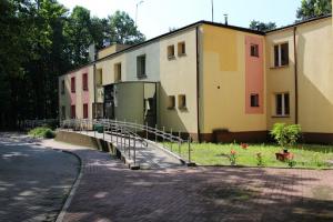 Zdjęcie przedstawiające kolorowy budynek - Dom Pomocy Społecznej. Przed budynkiem widać fragment trawnika oraz podjazd dla osób na wózkach.