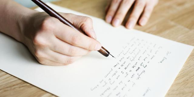 Na zdjęciu widać leżącą na stole zapisaną kartkę papieru oraz dłonie. W prawej dłoni jest pióro. Lewa dłoń przytrzymuje kartkę.
