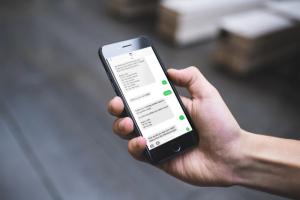 Na zdjęciu widać dłoń z telefonem komórkowym. Na ekranie telefonu widać wiadomości sms.