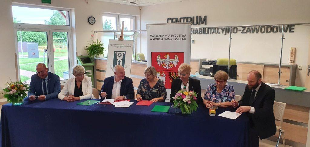 Przy długim stole siedzą przedstawiciele Koła PSONI w Biskupcu oraz Marszałek Województwa Warmińsko-Mazurskiego i podpisują dokumenty